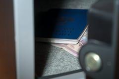 Bargeld-Depotverwahrung Kleine Wohnwölbung mit Bargeld und Pass Weitwinkelobjektiv bedeckt durch Linsen-Kappe in der Mitte Stockfoto