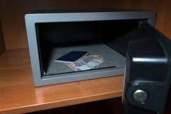 Bargeld-Depotverwahrung Kleine Wohnwölbung mit Bargeld und Pass Weitwinkelobjektiv bedeckt durch Linsen-Kappe in der Mitte Lizenzfreies Stockfoto