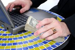 Bargeld in der Hand, das auf Tabellen-oberstem nahem Laptop stillsteht Stockfoto