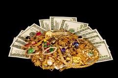 Bargeld mit Goldschmucksachen auf schwarzem Tuch-Hintergrund Stockfotos