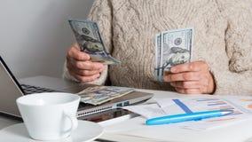 Bargeldrechnungen von USA-W?hrung Dollar ?ltere Person, die Rechnungen auf Schreibtisch behandelt lizenzfreies stockfoto