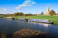 Barges on Nene River at Fotheringhay. River view of Fotheringhay Church and barges on Nene, Northamptonshire Stock Images