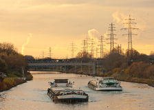 Barges plying waterway channel in industrial area royalty free stock photography