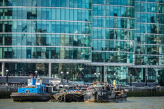 Barges on river Thames. Three barges on river Thames with London glass modern commercial buildings in the background stock photography
