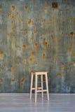 Barhockerstuhl auf Betonmauer mit Roststellen Lizenzfreies Stockbild