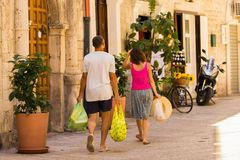 BARI, ITÁLIA - 11 DE JULHO DE 2018, um homem e uma mulher voltados com compras, uma cena da vida quotidiana na rua de Bari velho, foto de stock royalty free