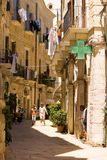 BARI, ITALY - JULY 11, 2018, street thermometer shows 32 degrees Celsius, summer heat. View of a narrow street in the Italian city royalty free stock images
