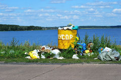 Baril de débordement avec des déchets et élimination des déchets sur le waterf Photographie stock