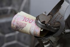 Baril en métal et argent ukrainien, le concept du coût d'essence, diesel, gaz Remplissage de la voiture Rouleau des billets de ba images stock