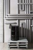Baril et tuyauterie noirs - concept Réseau de pipe-lines argenté dans l'usine de pétrole brut photographie stock