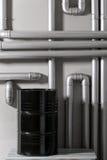 Baril et tuyauterie noirs - concept Réseau de pipe-lines argenté dans l'usine de pétrole brut image stock