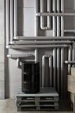 Baril et tuyauterie noirs - concept Réseau de pipe-lines argenté dans l'usine de pétrole brut photographie stock libre de droits