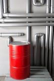 Baril et tuyauterie rouges - concept Réseau de pipe-lines argenté dans l'usine de pétrole brut photos stock