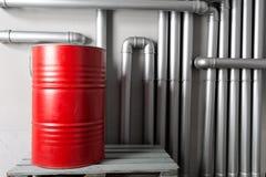Baril et tuyauterie rouges - concept Réseau de pipe-lines argenté dans l'usine de pétrole brut photo stock