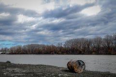 Barile da olio arrugginito in riva del fiume immagine stock