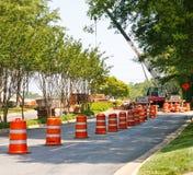 Barilotti arancioni e bianchi nella costruzione di strade Immagine Stock Libera da Diritti