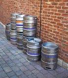 Barilotti di birra di alluminio contro un muro di mattoni Fotografia Stock