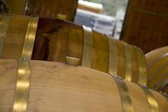 Barilotti di vino con il tappo impilato nell'area della cantina della serra di viti Fotografia Stock