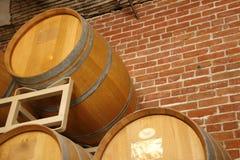 Barilotti di vino impilati nell'area della cantina della serra di viti Immagine Stock