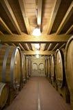Barilotti di vino impilati nella vecchia cantina Fotografie Stock Libere da Diritti
