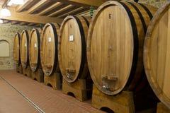 Barilotti di vino impilati nella vecchia cantina Fotografia Stock