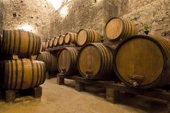 Barilotti di vino impilati nella vecchia cantina della cantina immagini stock libere da diritti