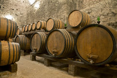 Barilotti di vino impilati nella vecchia cantina della cantina, Fotografia Stock