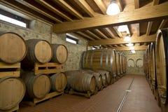 Barilotti di vino impilati nella vecchia cantina della cantina, Fotografie Stock