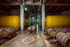 Barilotti e cisterna di legno del metallo con vino dentro la vecchia cantina della casa vinicola di Kindzmarauli Corporation Fotografie Stock