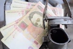 Barilotto del metallo e soldi ucraini, il concetto del costo di benzina, diesel, gas Riempimento dell'automobile fotografia stock