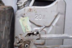 Barilotto del metallo e soldi ucraini, il concetto del costo di benzina, diesel, gas Riempimento dell'automobile 20 litri e banco fotografia stock libera da diritti