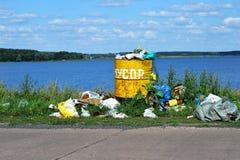 Barilotto di straripamento con rifiuti e smaltimento dei rifiuti sul waterf Fotografia Stock