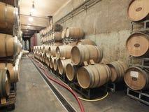 Barils de vin empilés dans la cave de l'établissement vinicole Images libres de droits