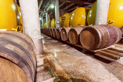 Barils de vin et réservoirs en métal dans la cave foncée de l'établissement vinicole photographie stock libre de droits