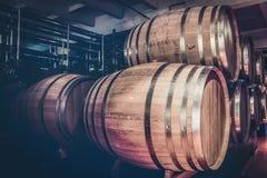 Barils en bois avec le cognac dans la cave foncée images libres de droits