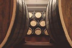 Barils en bois avec le whiskey dans la cave fonc?e images stock