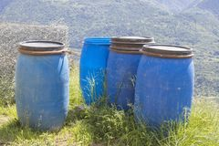 Barils et déchets bleus dans la nature et un ciel bleu Images stock