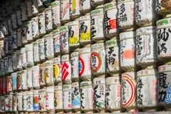 Barils japonais de saké enveloppés en paille empilée sur l'étagère Photo stock