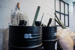 Barils noirs de vieille huile sur la brique grunge blanche images stock