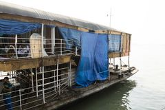 Barisal, Bangladesh, February 27 2017: The Rocket - an ancient paddle steamer. Had suffered a collision at the stern. The damage is now covered with a blue royalty free stock images