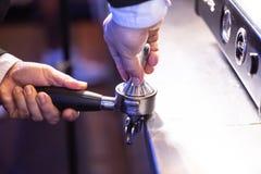 Barista举行portafilter和咖啡堵塞器做咖啡在咖啡馆 免版税库存图片