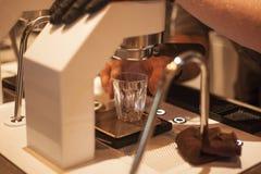 Barista从机器射击的酿造浓咖啡 免版税库存图片