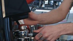Barista作为在小组的咖啡研磨,准备对酿造浓咖啡射击 免版税库存照片