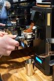 Barista倒碾碎的咖啡入持有人 免版税库存照片
