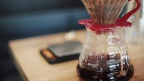 Barista准备倾吐,滴下热的新鲜的咖啡的Chemex,被过滤 烧瓶被称 股票录像