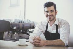 Barista准备在他的咖啡店的热奶咖啡 库存图片