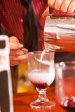 Barista手倾吐牛奶泡沫入从咖啡罐的新近地煮熟的咖啡在透明玻璃杯子,照片 免版税库存图片