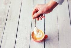 Barista拿着有coffe的可口奶油的` s手一把匙子 免版税库存照片
