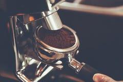 Barista的手投入了portafilter到brewin的煮浓咖啡器 库存图片
