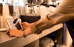 Barista är handen genom att använda ipad med skjuten espresso i bakgrund royaltyfri bild